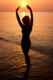Sunrise silhouette of a woman. On sea  beach Royalty Free Stock Photography