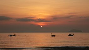 Sunrise Sky With Fishing Boats. A fiery orange morning sky looking out over the south China sea in Vung Lam Bay Vietnam. With a fishing boats silhouette and the stock footage