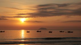 Sunrise Sky With Fishing Boats. A fiery orange morning sky looking out over the south China sea in Vung Lam Bay Vietnam. With a fishing boats silhouette and the stock video