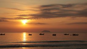 Sunrise Sky With Fishing Boats. A fiery orange morning sky looking out over the south China sea in Vung Lam Bay Vietnam. With a fishing boats silhouette and the stock video footage