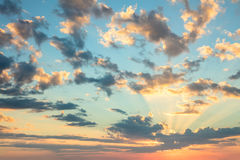 Sunrise sky, gentle colors of soft clouds and sunshine with rays Stock Photos