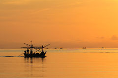 Sunrise with Small fishing boat Stock Photos