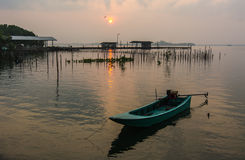 Sunrise and a small fishing boat in the river. Stock Image