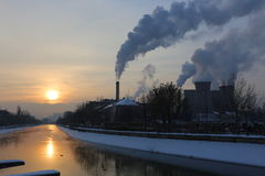 Sunrise and smoke from factory chimneys in winter. Stock Photography