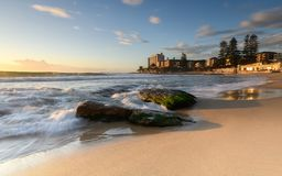 Sunrise at South Cronulla Beach in Sydney. With flowing waves breaking on he sandy beach royalty free stock photos