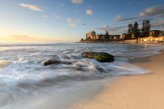 Sunrise at South Cronulla Beach in Sydney. With flowing waves breaking on he sandy beach royalty free stock photography