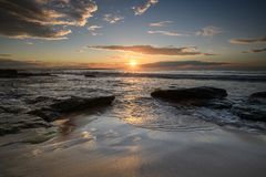 Sunrise at South Cronulla Beach in Sydney. With flowing waves breaking on he sandy beach royalty free stock photo