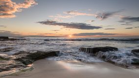 Sunrise at South Cronulla Beach in Sydney. With flowing waves breaking on he sandy beach stock image