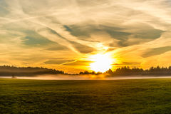 Sunrise and spindrift clouds over the forest and the field Royalty Free Stock Photo