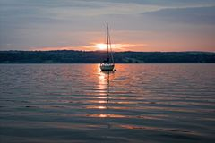 Sunrise spotlight on the sailboat stock photos