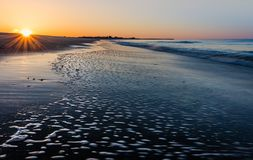 Sunrise starburst at Cape May, NJ, beach as low tide flows across the sand. With wide angle Royalty Free Stock Photos