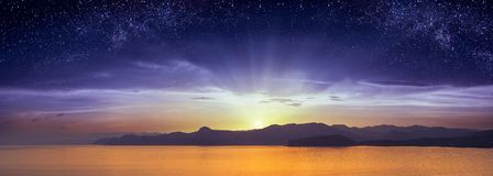 The sunrise with starry sky above the Crimea. The meating of day and night above the sea and mountains of Crimea. The sunrise with starry sky. Fantastic Stock Photos