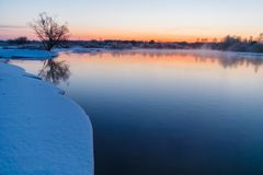 Sunrise starting over river in winter time. Rural landscape royalty free stock images
