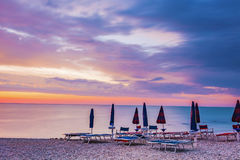 Sunrise in a stony beach. With umbrellas and sunbeds Stock Image