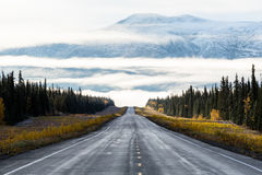 Sunrise on straight road into fog below peak. Early morning light illuminates this northern scene in the Yukon Territory of Canada. A two lane road disappears Stock Photos