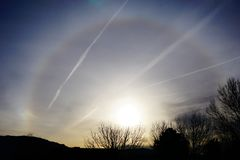 Sunrise with strange circle around the sun. A picture of a strange sunrise in New Mexico with a circle around the sun and jet streams across the sky Stock Image