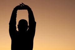 Sunrise Stretch. Silhouette of man at sunrise stretching royalty free stock photography