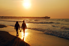 Sunrise Stroll. Two women stroll the shoreline of Myrtyle Beach, South Carolina at sunrise stock images