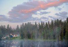 Sunrise of summer northern white night on small lake in forest Stock Photos