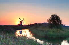 Sunrise with sun behind Dutch windmill Stock Images