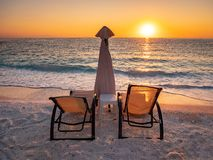 Sunrise with sun chairs and umbrella on the seashore at Marble Beach on the Greek Island Thasos in the Aegean Sea. Thasos or Thassos Island is a summer royalty free stock photo