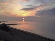 Sunrise sun ocean sea groin beach stone reflection clouds United Kingdom stock photo