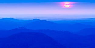 Sunrise sun peeks through the clouds over mountain range. Sunrise sun peeks through the clouds over  mountain range Stock Photo