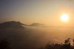 Sunrise. Sun shining over a sea mist and mountain Stock Images