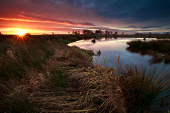 Sunrise sunbeams over swamp in autumn Stock Photo