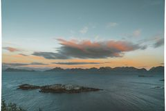 Sunrise and Sunset at Henningsvaer over atlantic ocean with pink clouds. The fishing village located on several small. Islands in the Lofoten archipelago royalty free stock photography