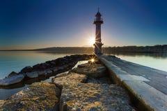 Sunrise Sunstar on Lake Geneva at Paquis Lighthouse, Geneva, Switzerland Royalty Free Stock Photos