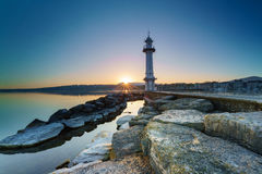 Sunrise with sunstar at Paquis Lighthouse, Geneva city. Royalty Free Stock Images
