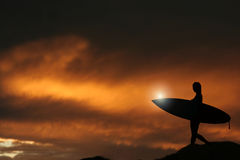 Sunrise Surfer. Silhouette of a surfer heading into the water during sunrise Royalty Free Stock Photography