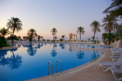 Sunrise on swimming pool. Sunrise on resort swimming pool with lounge chairs Royalty Free Stock Photography