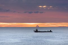 Sunrise In Tauranga, New Zealand. The early morning view of an industrial ship floating by with a cloudy sky in a background Tauranga, New Zealand Stock Images