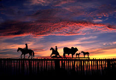 Sunrise and Texas ranch gate. Silhouette of ranch gate against brightly colored sunrise royalty free stock photos