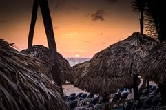 Sunrise and a thatched palm frond palapa royalty free stock photos