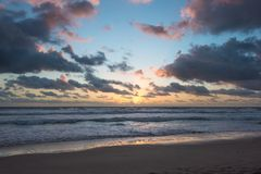 Sunrise on tropical beach. With colorful sky and mild waves on sandy shore. Nature background Stock Photo
