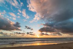 Sunrise on tropical beach. With colorful sky and mild waves on sandy shore. Nature background Royalty Free Stock Photos