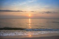 Sunrise at  tropical calm sea in Hua Hin, Thailand. Beautiful golden sunrise over skyline at  tropical calm sea with sand beach wave  and blue sky in Hua Hin stock photos