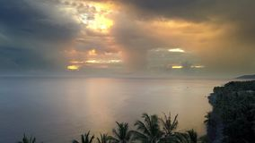 Sunrise on the tropical sea. Aero shooting from the drone,The coast with palm trees, the Sun to shine through clouds. Fishing boats in the sea stock footage