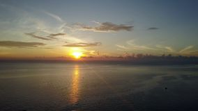 Sunrise on the tropical sea. Aero shooting from the drone,The coast with palm trees, the Sun to shine through clouds. Fishing boats in the sea stock video