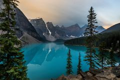 Sunrise with turquoise waters of the Moraine lake with sin lit rocky mountains in Banff National Park of Canada in royalty free stock image