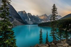 Sunrise with turquoise waters of the Moraine lake with sin lit rocky mountains in Banff National Park of Canada in stock photo