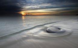 Sunrise and tyre at Batu Buruk beach Royalty Free Stock Image