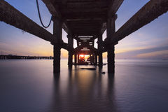 Sunrise under the old fishing pier Stock Images