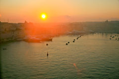 Sunrise, Valetta Harbor, Malta. A sunrise over the harbor at Valetta, capital of Malta.  Pleasure boats are moored on the left and the mooring buoys are in front Royalty Free Stock Photography