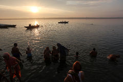 Sunrise at Varanasi. Devotees take a holy dip at dawn in Ganges River or Ganga River along the ghats of Varanasi, Uttar Pradesh, India Royalty Free Stock Image