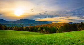 Sunrise in Vermont in the fall. With open grassy field in the foreground Stock Photo