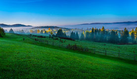 Sunrise in Vermont. Vermont in the fall with the sun rising over a field and a distant forest Royalty Free Stock Images